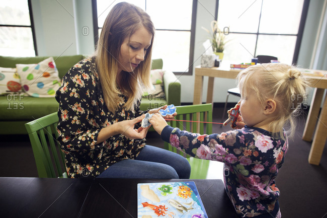 Woman and girl learning with puzzle
