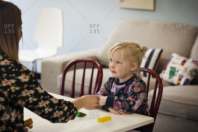 Young girl looking at woman in preschool