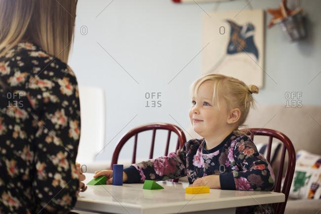Young girl looking at teacher in preschool