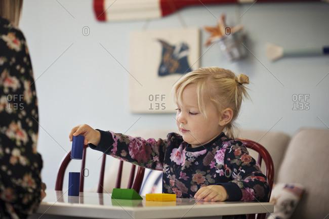 Girl stacking blocks at preschool table