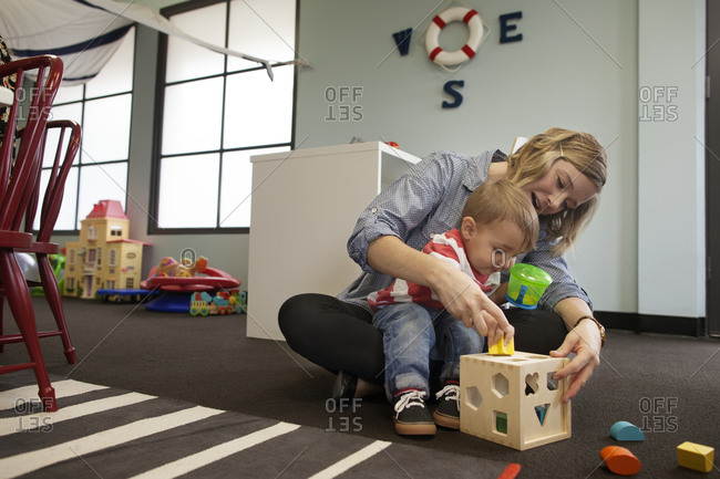 Woman guiding toddler with shape blocks