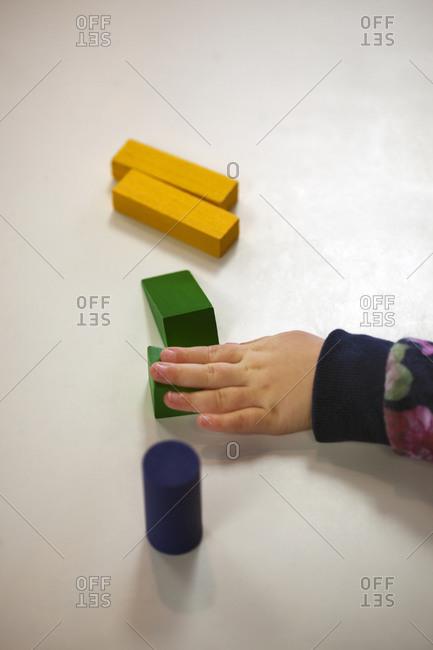 Hands arranging blocks on preschool table