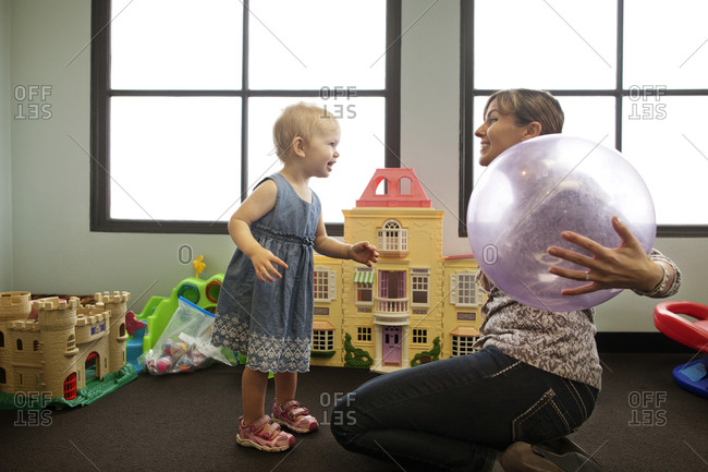 Toddler and woman with ball in daycare
