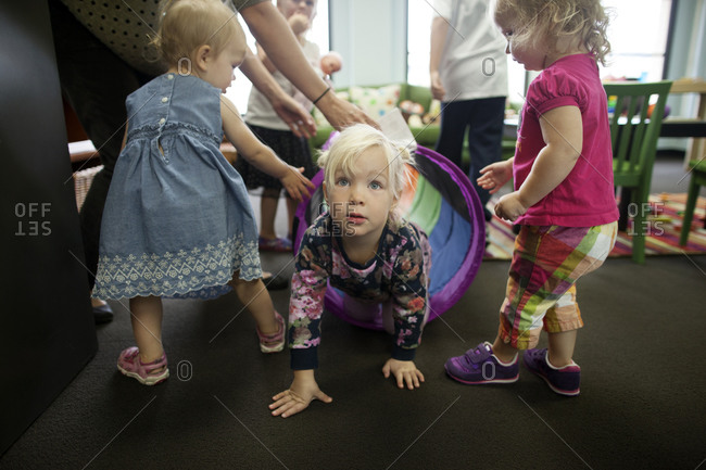Toddlers playing with tunnel in daycare