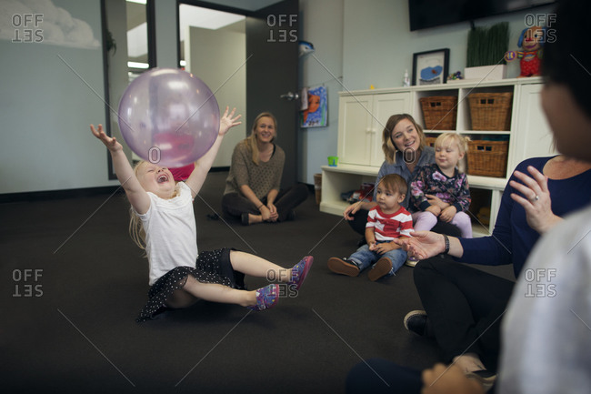 Girl in daycare laughing catching ball