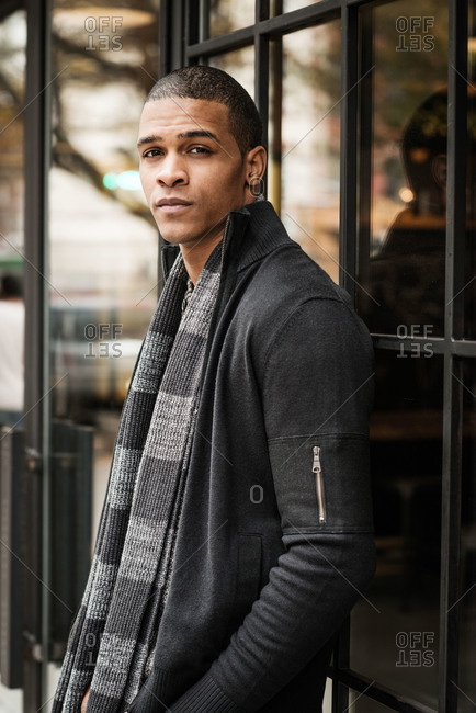 Portrait of young man leaning against storefront