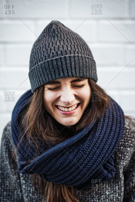 Portrait of woman laughing by brick wall