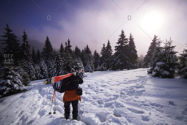 Man carrying skis through snowy wilderness