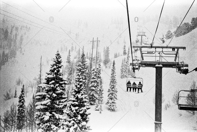 People riding ski lift up snowy slope