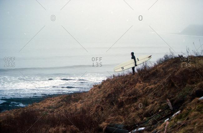 Man standing on Nova Scotia coast with surfboard