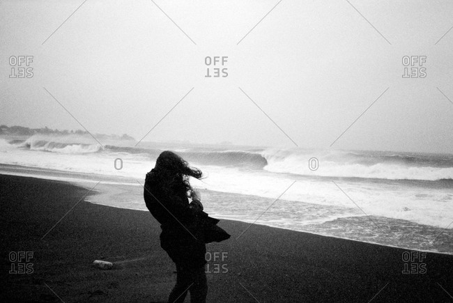 Woman standing on cold windy beach