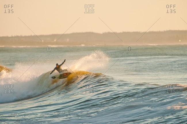 Surfer riding wave in Nova Scotia