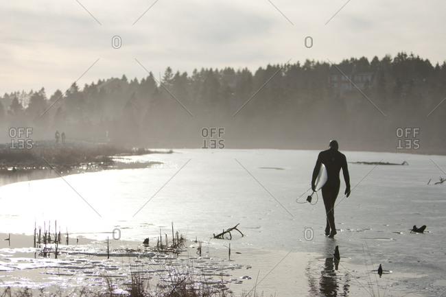 Surfer walking foggy Nova Scotia beach
