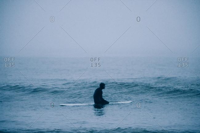 Surfer sitting in foggy Nova Scotia ocean