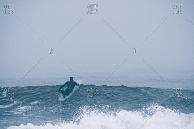 Surfer paddling in foggy Nova Scotia ocean