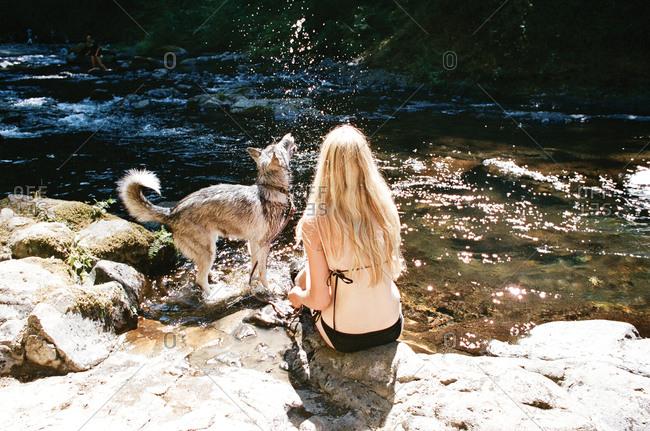 Woman in bikini with dog on river bank