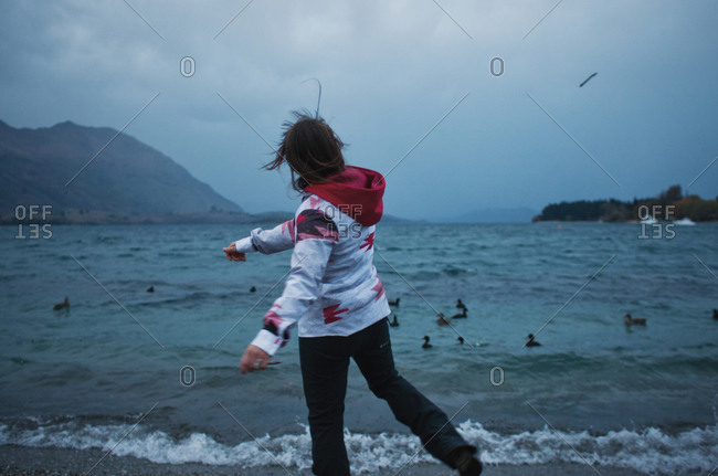 Woman throwing stick out to sea