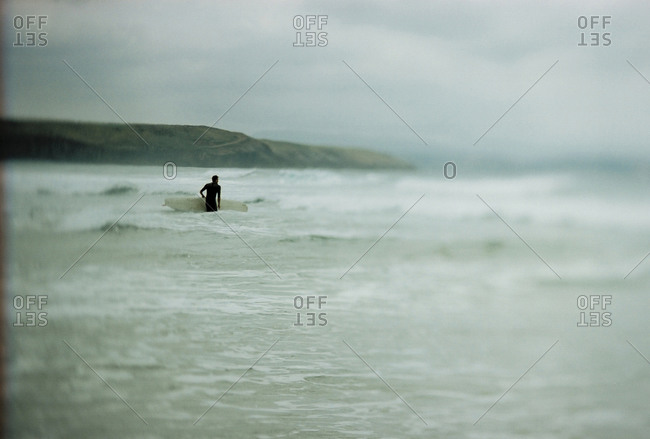Surfer with board wading in Spanish sea