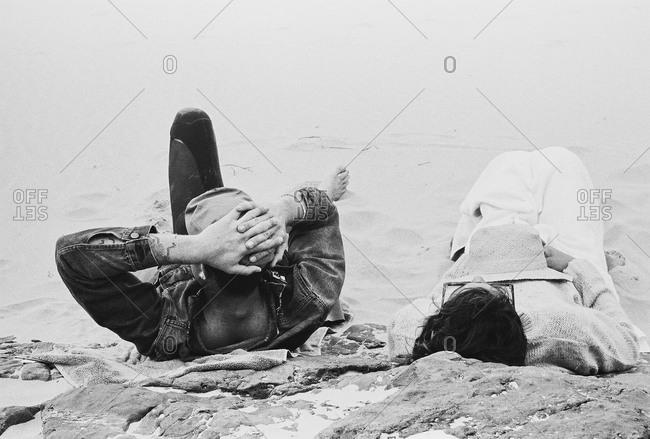 Couple lounging on rocky Spanish beach