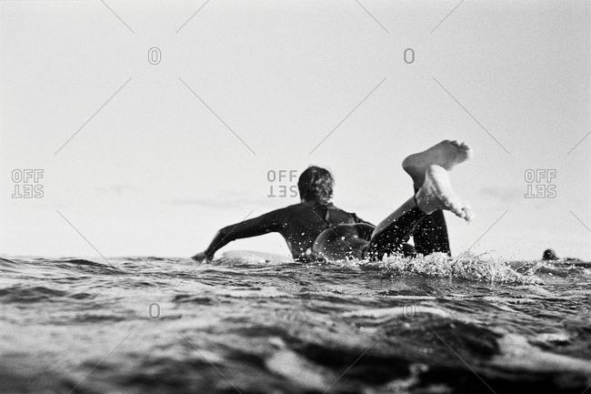 Man in wetsuit paddling on surfboard