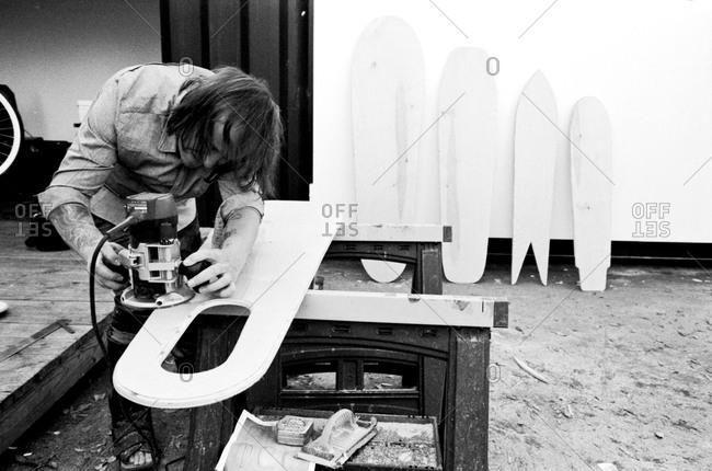 Man in workshop sanding surfboard