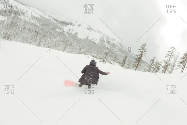 Man snowboarding snowy Lake Tahoe hill