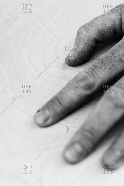 Man's hand on handmade surfboard
