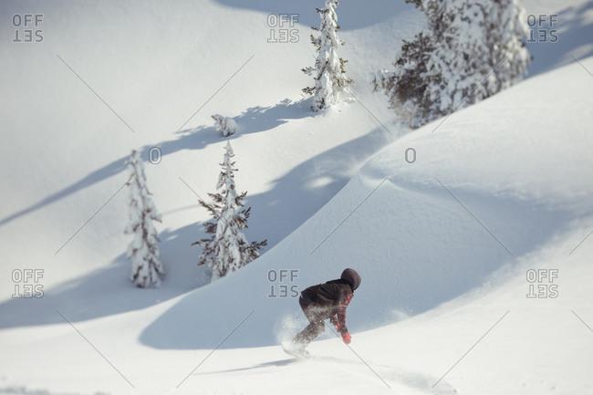 Snowboarder blazing trail in pristine snow