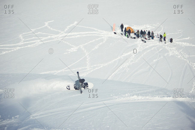 Snowboarder reaching friends at base
