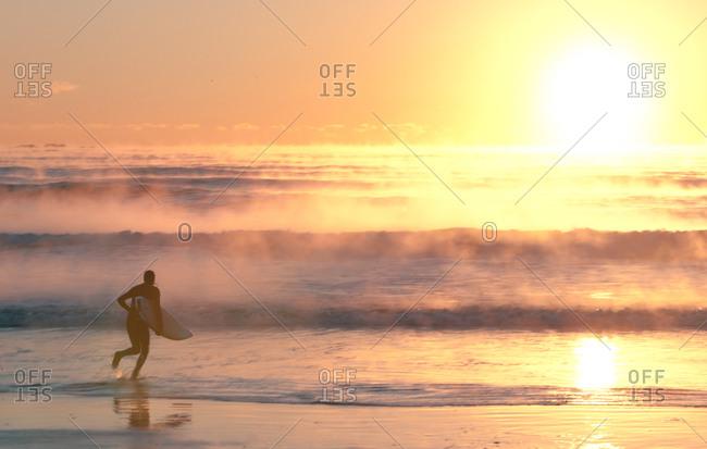 Surfer running with board on foggy beach