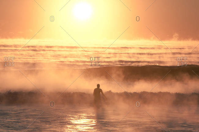 Surfer wading in foggy waves