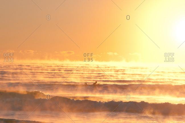 Surfer in foggy sea