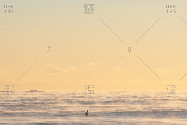 Surfer out in foggy sea