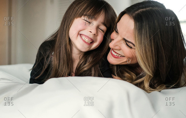 Mom and daughter giggling on bed