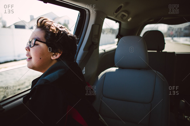 Young boy staring out of a car window