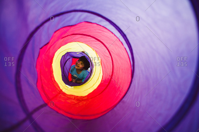 Young boy crawling in a play tunnel