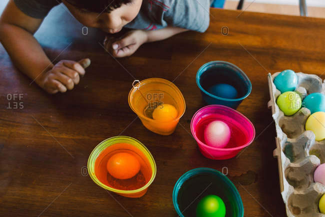 Young boy coloring Easter eggs at a table
