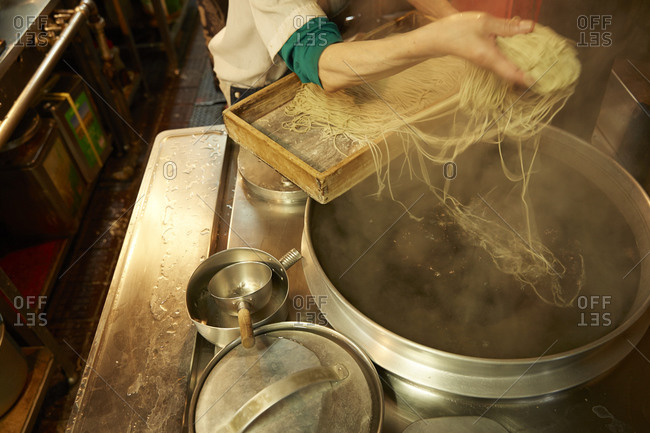 A woman throws raw ramen noodles into a pot of boiling water