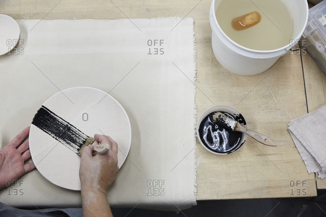 A woman paints a stripe across a ceramic plate