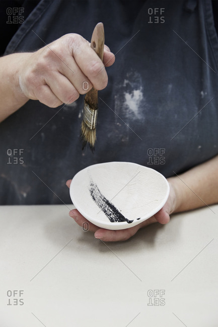 A woman paints a black stripe onto a white bowl