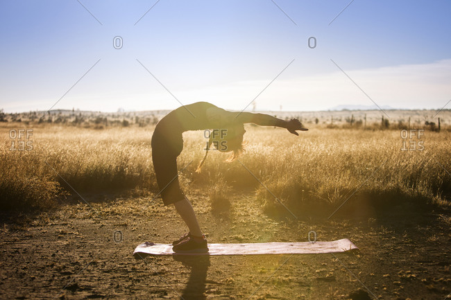 Woman on yoga mat in field doing back bend