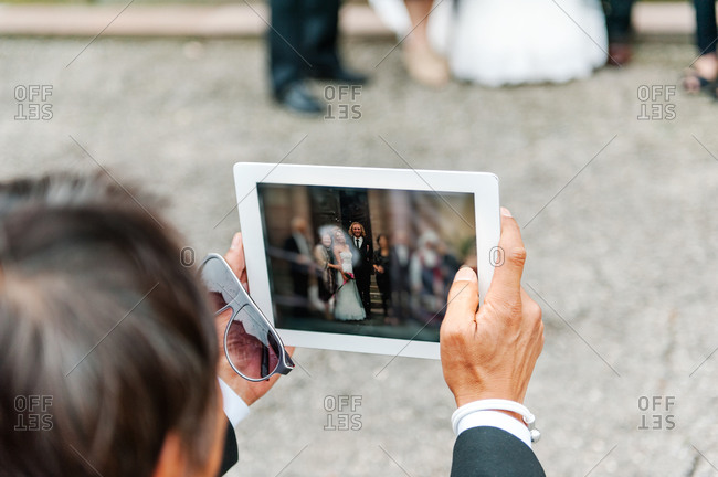 Guest taking a wedding group photo with a digital tablet on the stairs of the church