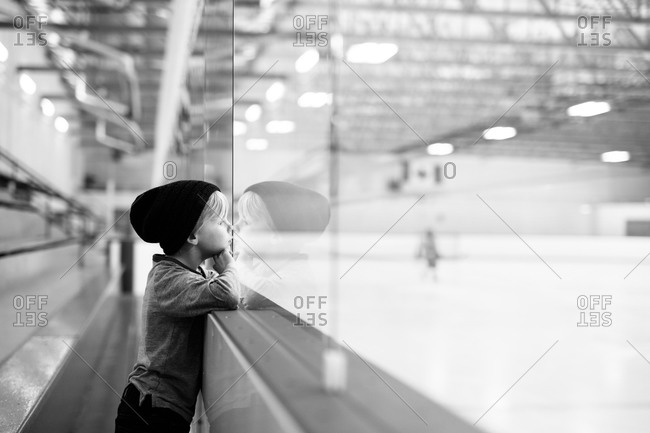 Boy in hockey rink staring at ice