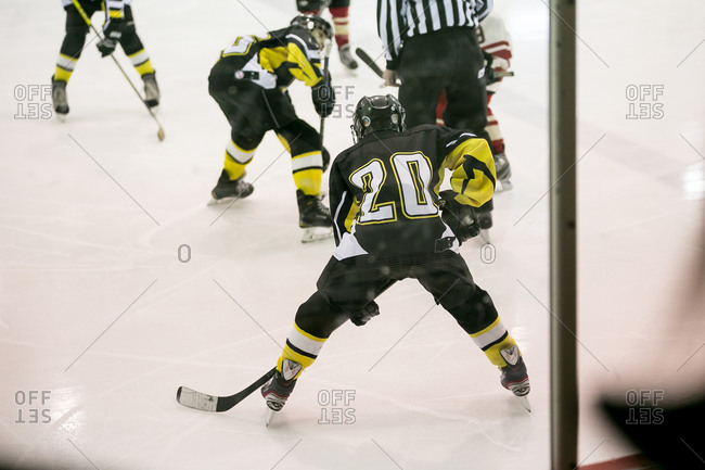 Youth hockey players and referee on ice
