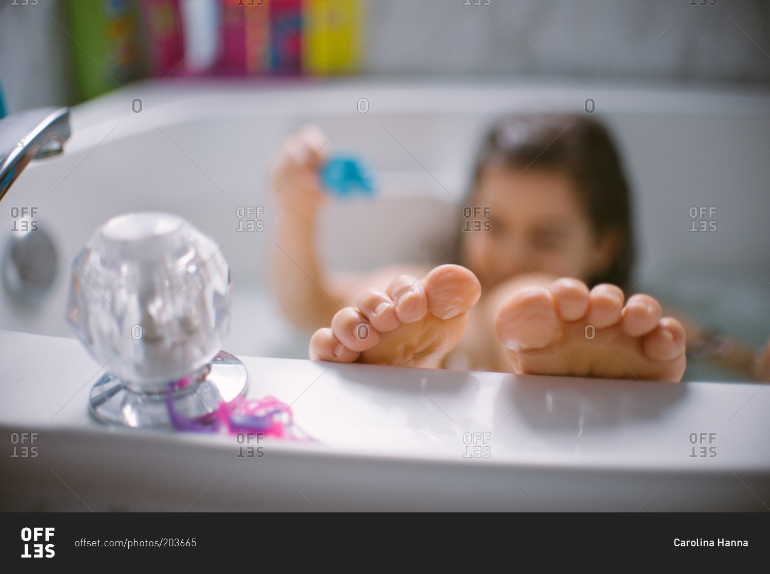 Girl playing in the bathtub with feet on edge of tub stock photo ...