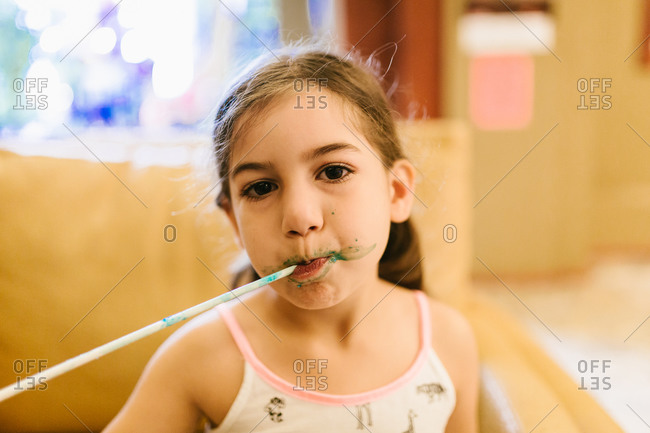 Young girl with long straw and sugary blue treat on her face