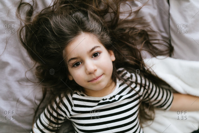 Beautiful young girl with tousled dark hair lying on bed