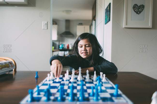 Enthusiastic young girl playing chess