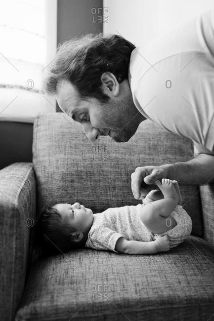 A dad peers at his newborn baby
