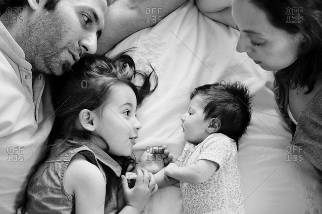 A family lays around their newborn baby